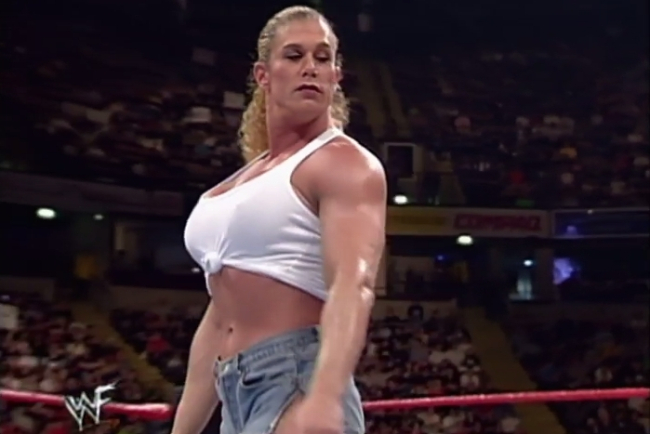 Nicole Bass - a large, muscled blonde woman - standing in a wrestling ring.