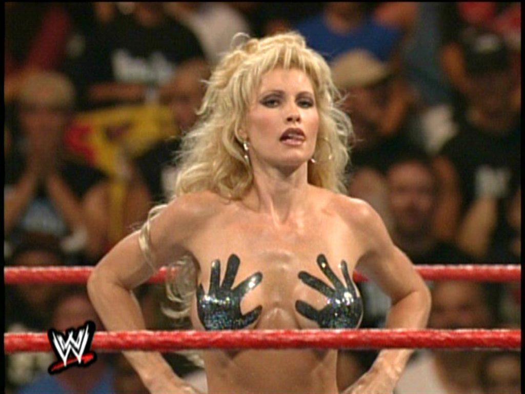 Wrestler Sable (blonde, white woman, thin & athletic), topless with handprints painted on her breasts as part of a bikini contest